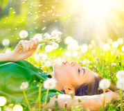 Härlig kvinna som ligger på fältet i grönt gräs och blåser maskrosen Fotografering för Bildbyråer