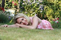 Härlig kvinna som ligger på gräset Fotografering för Bildbyråer