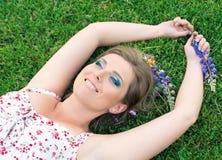 Härlig kvinna som ligger på gräset och le Fotografering för Bildbyråer