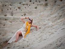 Härlig kvinna som ligger på sanden Arkivbild