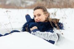 Härlig kvinna som ligger på snö Arkivbilder