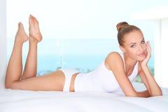 Härlig kvinna som ligger på vit säng Arkivfoton
