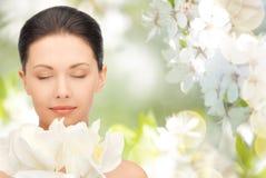 Härlig kvinna som luktar blommor med stängda ögon Fotografering för Bildbyråer
