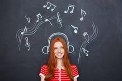 Härlig kvinna som lyssnar till musik i hörlurar som dras på den svart tavlan Royaltyfri Foto