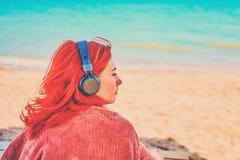 Härlig kvinna som lyssnar till musik på stranden royaltyfri fotografi