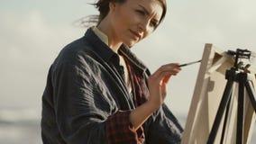 Härlig kvinna som målar bilden på banken av havet lager videofilmer