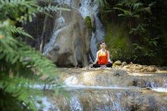 Härlig kvinna som mediterar på stenen royaltyfria bilder