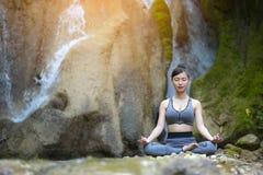Härlig kvinna som mediterar på stenen arkivbild