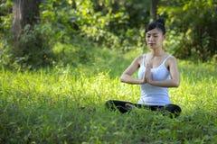 Härlig kvinna som mediterar på stenen arkivbilder