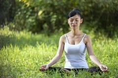 Härlig kvinna som mediterar på stenen royaltyfria foton