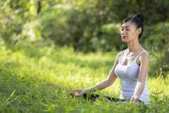 Härlig kvinna som mediterar på stenen royaltyfri fotografi