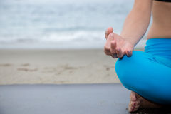 Härlig kvinna som mediterar på stranden Royaltyfri Foto