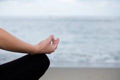 Härlig kvinna som mediterar på stranden Arkivfoton