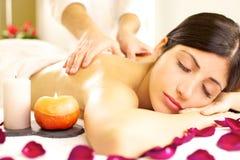 Härlig kvinna som mottar avslappnande massage i brunnsort Arkivbild