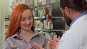 Härlig kvinna som mottar piller från hennes apotekare som shoppar på apoteket stock video