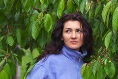 Härlig kvinna som nära står av ett körsbärsrött träd Arkivbilder