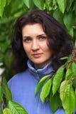 Härlig kvinna som nära står av ett körsbärsrött träd Arkivfoto