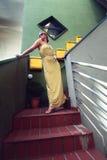 Härlig kvinna som poserar i den långa gula klänningen på terrassen Arkivfoto