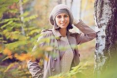 Härlig kvinna som poserar i ett björkträ Fotografering för Bildbyråer
