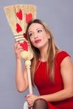 Härlig kvinna som poserar med röda hjärtor som göras av papper på broen royaltyfri foto