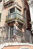 Härlig kvinna som poserar på en bro över kanalen i Venedig Arkivbilder