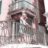 Härlig kvinna som poserar på en bro över kanalen i Venedig Fotografering för Bildbyråer