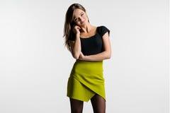 Härlig kvinna som poserar på en ljus bakgrund Den gröna kjolen Arkivbilder