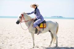 Härlig kvinna som rider en häst på stranden royaltyfri fotografi