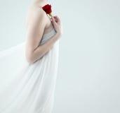Härlig kvinna som rymmer den röda rosen Royaltyfri Fotografi