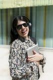 Härlig kvinna som rymmer en digital minnestavla, medan stå i set royaltyfria foton