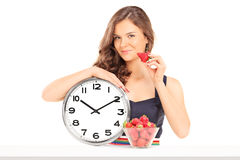 Härlig kvinna som rymmer en jordgubbe och en klocka Arkivbilder