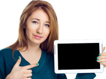 Härlig kvinna som rymmer en minnestavladator och visar på den svarta skärmen på vit bakgrund Arkivbilder