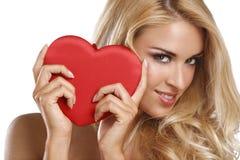 Härlig kvinna som rymmer en röd hjärta för valentin Arkivbilder