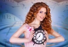 Härlig kvinna som rymmer en stor klocka royaltyfri fotografi
