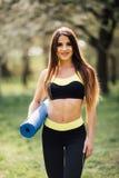 Härlig kvinna som rymmer mattt förbereda sig för blå yoga för övning Stående av en mogen le kvinna med kondition som är matt i pa Arkivbilder