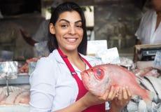 Härlig kvinna som säljer den nya fisken på en latinsk fiskmarknad Arkivfoto