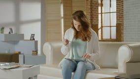 Härlig kvinna som sätter in kortnummer på minnestavlan, online-bankrörelse arkivfilmer