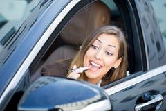 Härlig kvinna som sätter på läppstift i bil arkivfoton