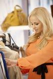 Härlig kvinna som söker bland kläder på lagret Arkivbilder