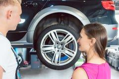 Härlig kvinna som ser lycklig på en pålitlig auto mekaniker arkivfoto