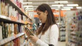 Härlig kvinna som ser skönhetsmedel i supermarket Attraktiva produkter för flickaköpandeskönhetsmedel lager videofilmer
