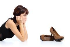 Härlig kvinna som ser skor för en stilett för höga häl Royaltyfri Bild