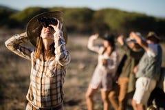 Härlig kvinna som ser till och med kikare under safarisemester arkivfoton