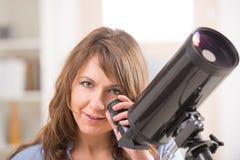 Härlig kvinna som ser till och med teleskopet royaltyfri bild