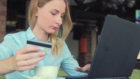 Härlig kvinna som shoppar direktanslutet genom att använda hennes kreditkort- och bärbar datordator stock video
