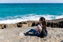 Härlig kvinna som sitter på kusten som håller ögonen på vågorna arkivbilder
