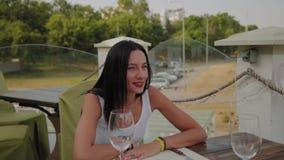 Härlig kvinna som sitter på tabellen på terrassen i restaurangen stock video