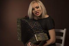 Härlig kvinna som sjunger med dragspelet Arkivfoto