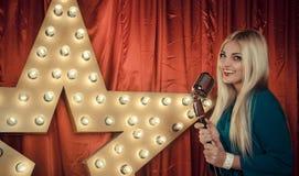 Härlig kvinna som sjunger på etapp med mikrofonen fotografering för bildbyråer
