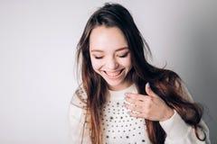 Härlig kvinna som skrattar och att le på en vit bakgrund Sinnesrörelser uttrycksfulla ansiktsbehandlingsärdrag royaltyfri bild